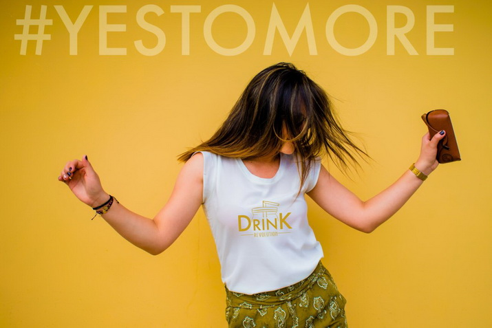 "Frau mit Drink Revolution-Shirt tanzt unter dem Hashtag ""Yes to more"""